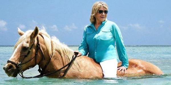 Martha Stewart in a hat and blue blouse sitting atop a horse walking through light blue water