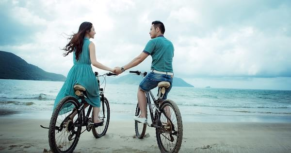 romance novels we'd love to see on the big screen, a couple riding  bikes down the beach, books
