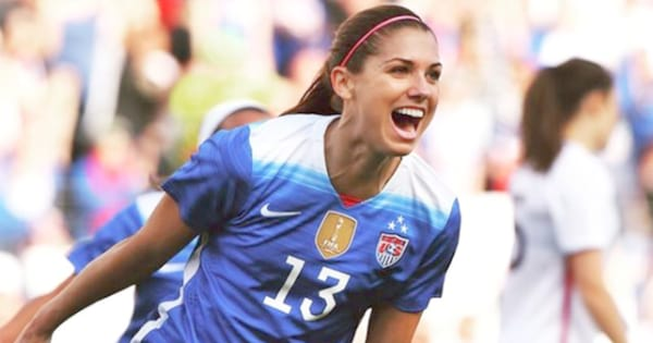 Alex Morgan smiling and running on the field after scoring a goal