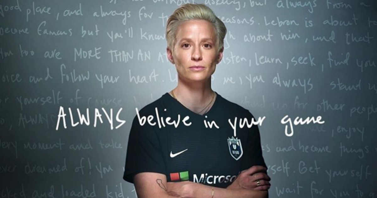 Megan Rapinoe posing in front of a blackboard with words written all over it