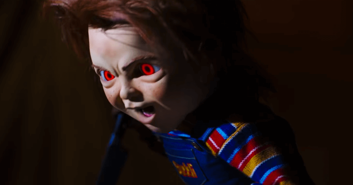 Chucky's eyes glaring red at someone while he holds a knife in one of his hands in 'Child's Play' (2019)