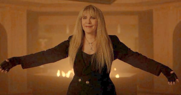 Stevie Nicks wearing all black and standing with her arms wide open in front of flames in 'American Horror Story: Apocalypse'