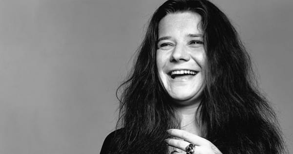 A black and white photo of Janis Joplin smiling while holding a cigarette in one hand