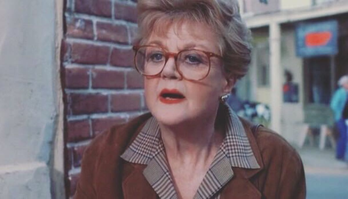 Angela Lansbury as Jessica Fletcher in 'Murder She Wrote' wearing big glasses, red lipstick, and a plaid button down underneath a brown coat