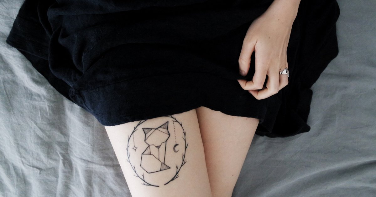 Girl showing off her geometric style fox tattoo on her thigh