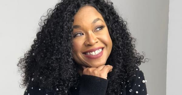 Shonda Rhimes in a black sweater with pearls all over it posing with her hand under her chin and smiling at something off camera