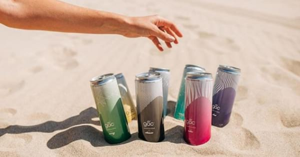 The entire line of Gac drinks positioned in the sand on the beach with a hand reaching for them