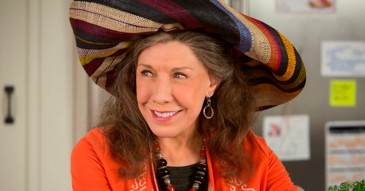 Lily Tomlin wearing a large sun hat and smiling at something offscreen in a scene from 'Grace and Frankie'