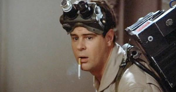 Dan Aykroyd smoking a cigarette that's falling out of his mouth in Ghostbusters