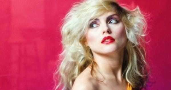 debbie harry from blondie band standing against red background quotes