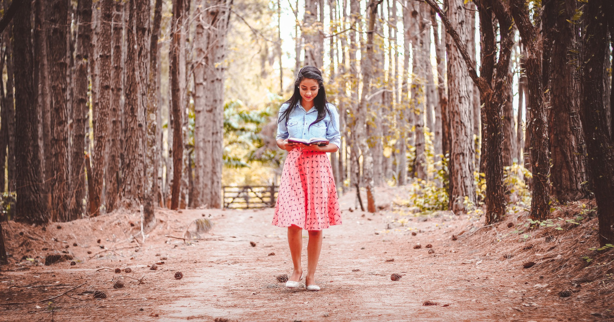 patriotic books, image of a brown woman with dark hair reading a book as she walks through woods, books
