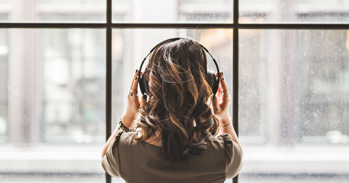 romance audio dramas, image of an asian woman with her back to the camera wearing headphones as she stares out windows, books, Music