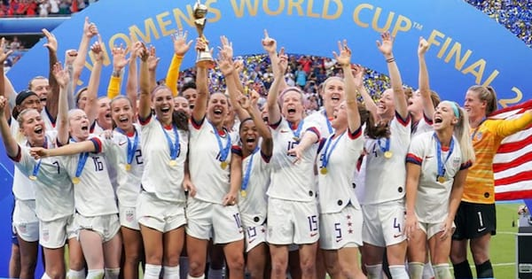 Team USA standing on a podium celebrating their 4th Women's World Cup win (2019)