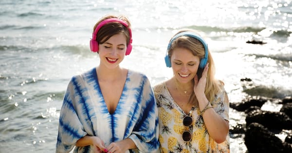 this sounds serious podcast, image of two white women wearing headphones standing with water behind them