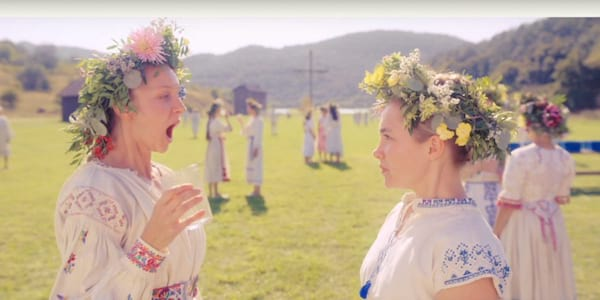 may queen scene from midsommar with two women in Swedish garb and flower crowns