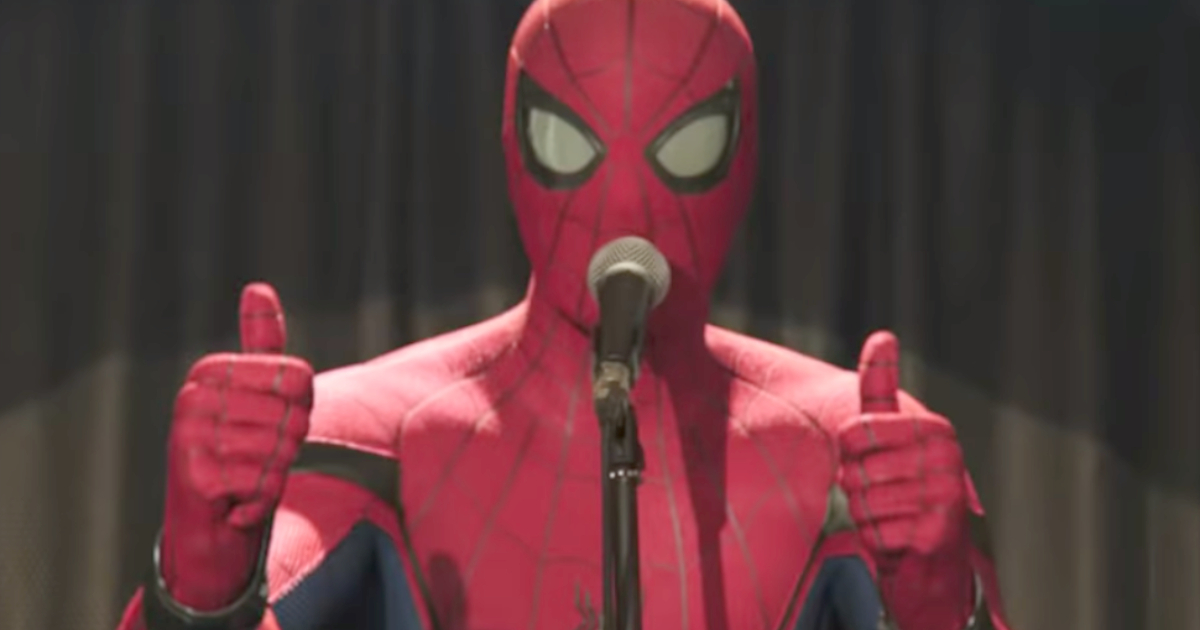 Spider-Man delivering a speech in front on a microphone while holding two thumbs up in 'Spider-Man: Far From Home'