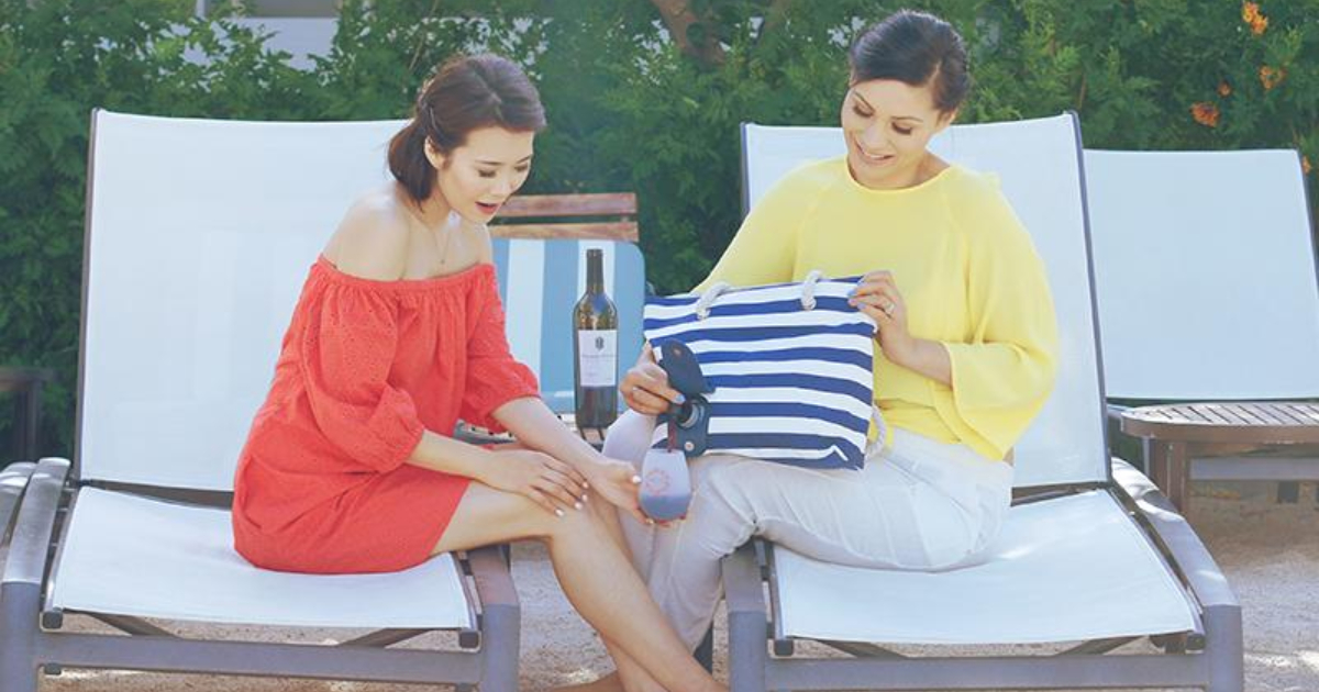 Two women pouring wine out of their Porto Vino purse while at the beach
