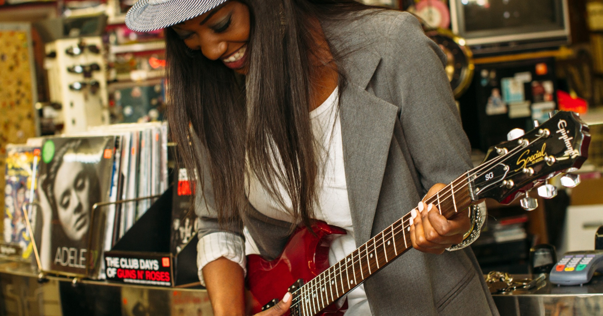 celebrity romance novels, a black woman with long straight hair wearing gray blazer plays a guitar, books