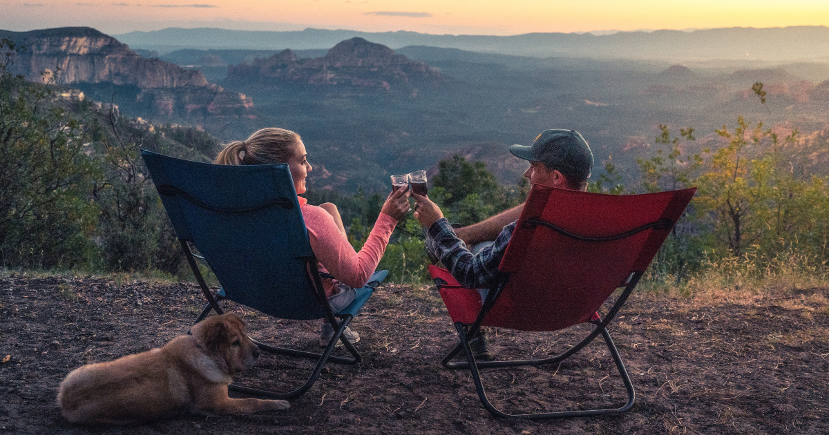 romance novels about animals, a couple sitting in chairs clink wine glasses with mountains in the background while their dog lies on the ground near them, books, animals