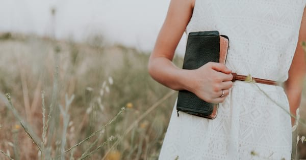 catholic bible quotes, image of a white woman in a white dress from roughly shoulders to knees holding a bible, books
