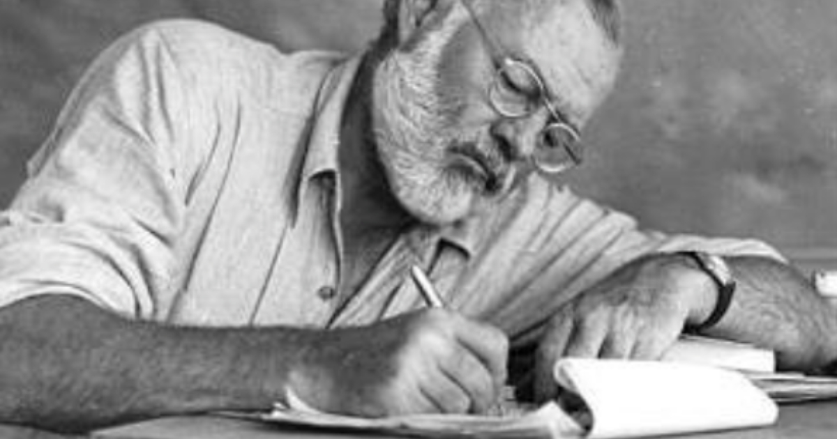 Ernest Hemingway writing on a piece of paper in a black and white photo