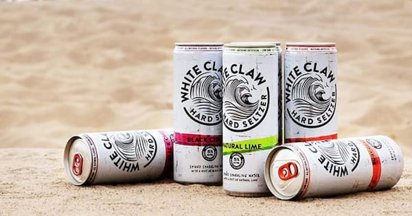 Five cans of White Claw sitting on the sand with people playing beach volleyball in the background