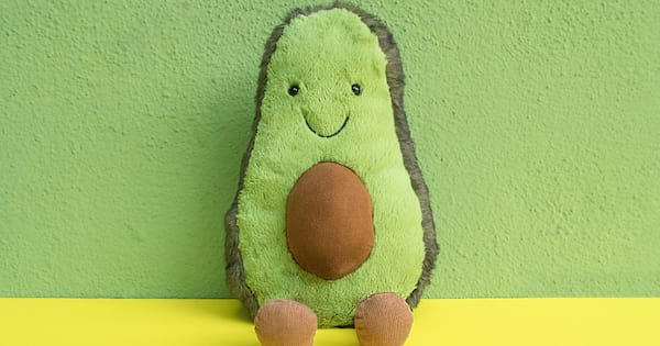 Avocado plush toy smiling while propped up on a green wall