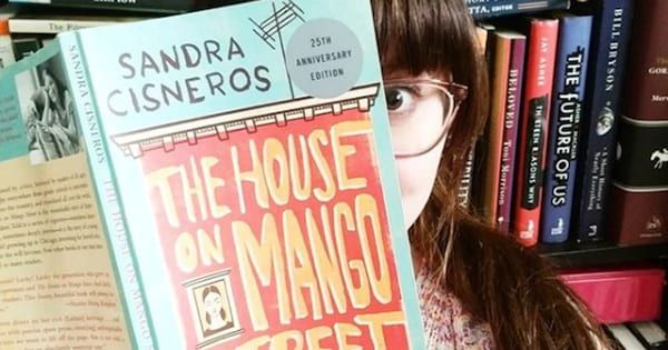 the house on mango street woman holding book up to face wearing glasses