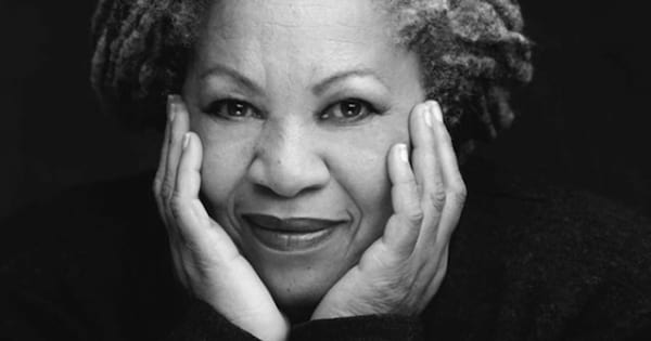 A black and white portrait of author Toni Morrison posing with her chin resting on both of her hands