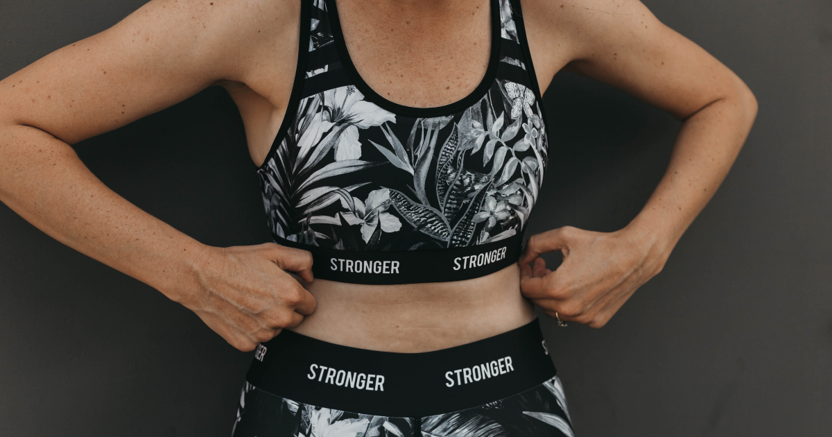 Woman wearing women's black and gray floral sports bra and leggings