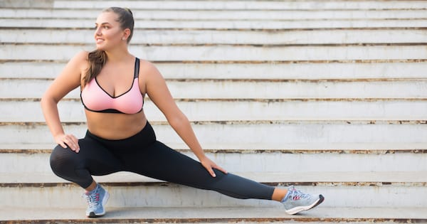 Beautiful smiling plus size girl in sporty top and leggings doing sport on stairs joyfully looking aside spending time outdoor