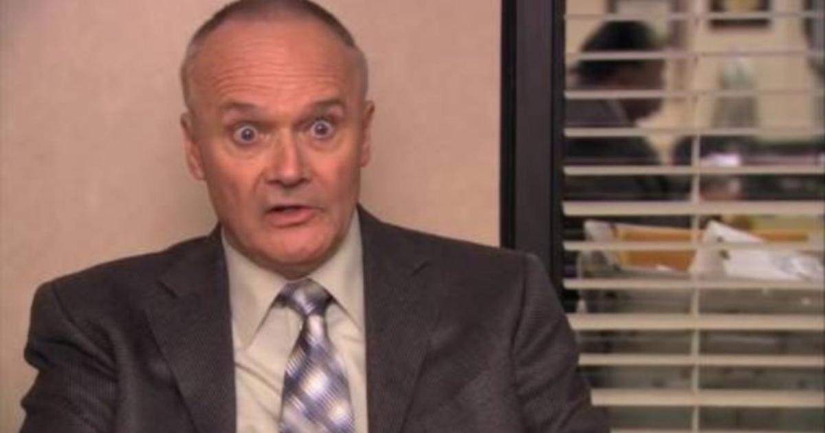 Creed sitting in a confessional for 'The Office' with his eyes bugged out