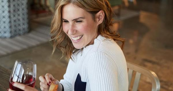 Feel Good Foods CEO Vanessa Phillips enjoying a class of red wine and Uncured Pepperoni Bites in an Instagram image