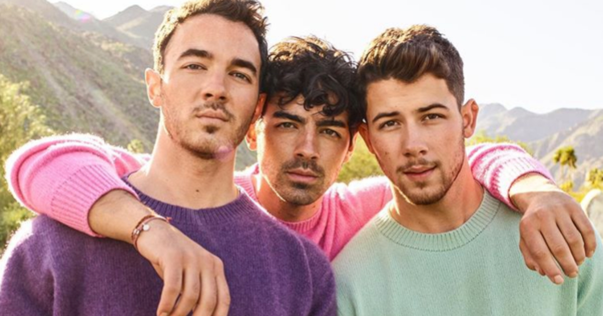The Jonas Brothers posing for an Instagram photo in colorful sweaters