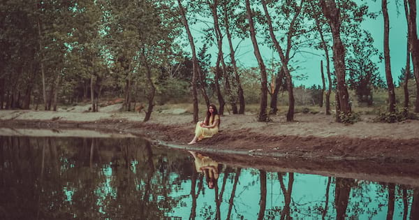 books like where the crawdads sing, image of a white woman sitting by the water reflecting, books