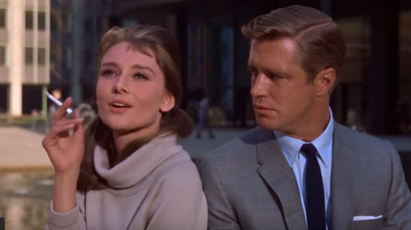 Aubrey Hepburn as Holly Golightly in Breakfast at Tiffany's smoking a cigarette next to costar George Peppard