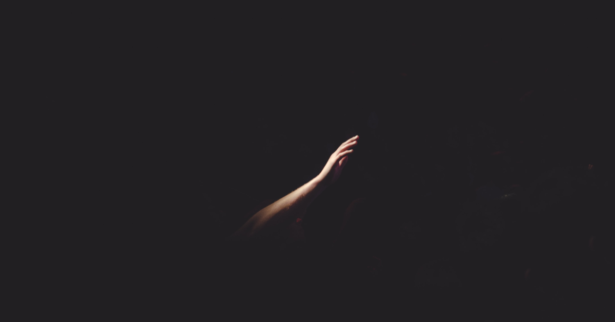 Right human hand reaching out of the darkness