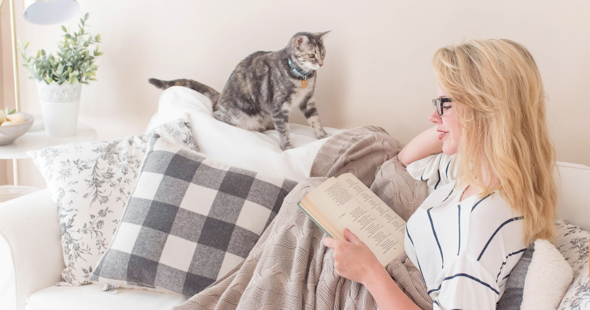romance awareness month books, a blonde woman reads a book with a cat, books