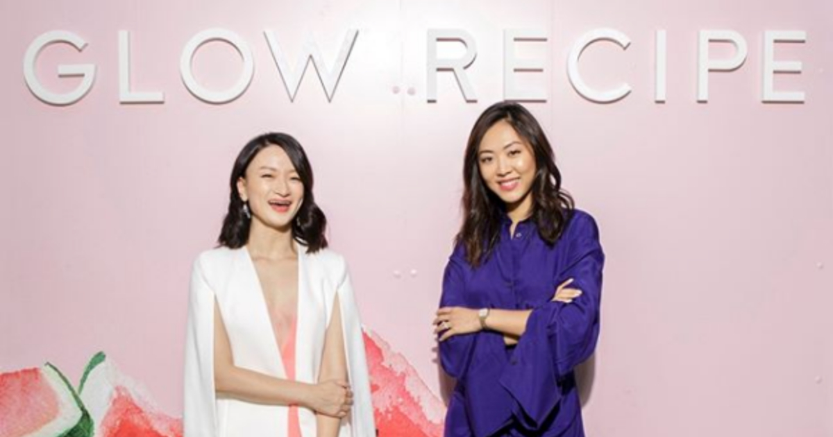 Glow Recipe co-founders Sarah Lee and Christine Chang standing in front of a pink back drop that reads 'Glow Recipe' at a Sephora event