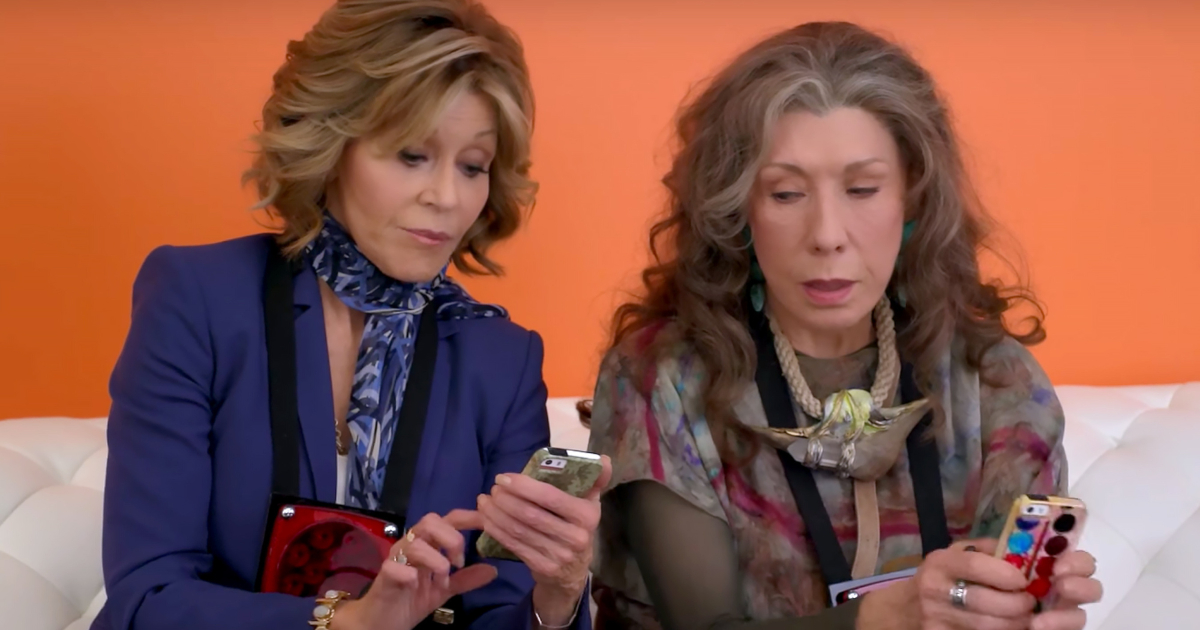Grace and Frankie looking at their phones in a scene from 'Grace and Frankie'