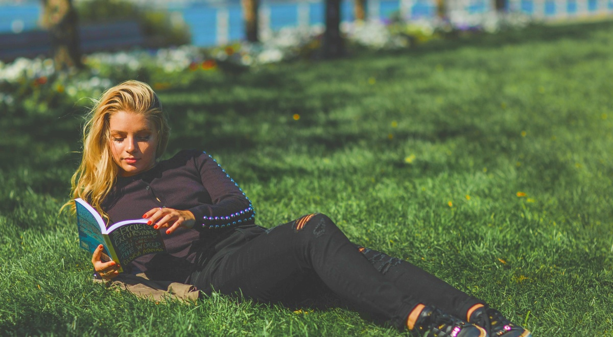 september romance releases, white blonde woman lying in grass reading book, books