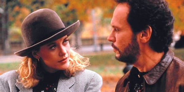 Meg Ryan wear a hat and jacket and Billy Crystal in a leather jacket walking in a park in When Harry Met Sally