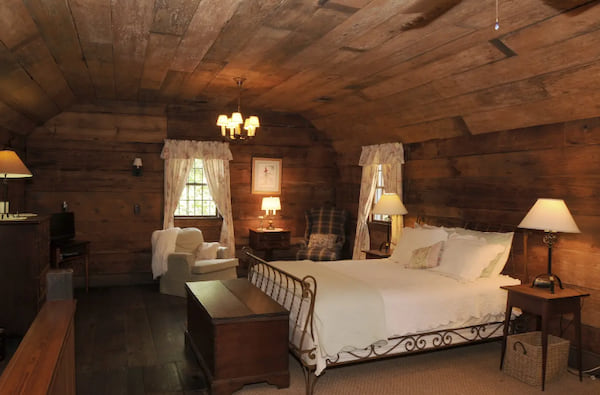 Original heart pine floors, walls and ceiling surround Queen bed and seating area upstairs in Laura's Cottage Airbnb listing
