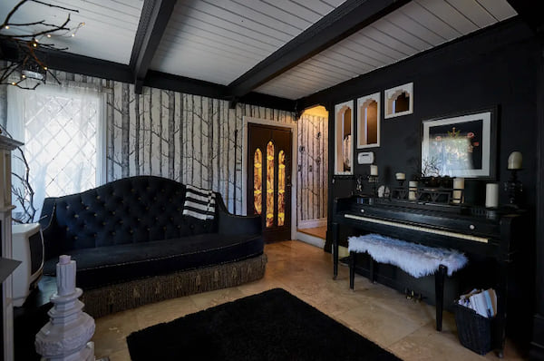 Living room complete with in-tune piano in The Crescent Manor listing on Airbnb