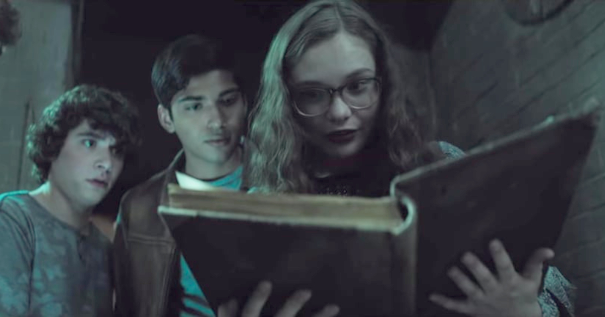 The kids reading from a book in 'Scary Stories to Tell in the Dark'