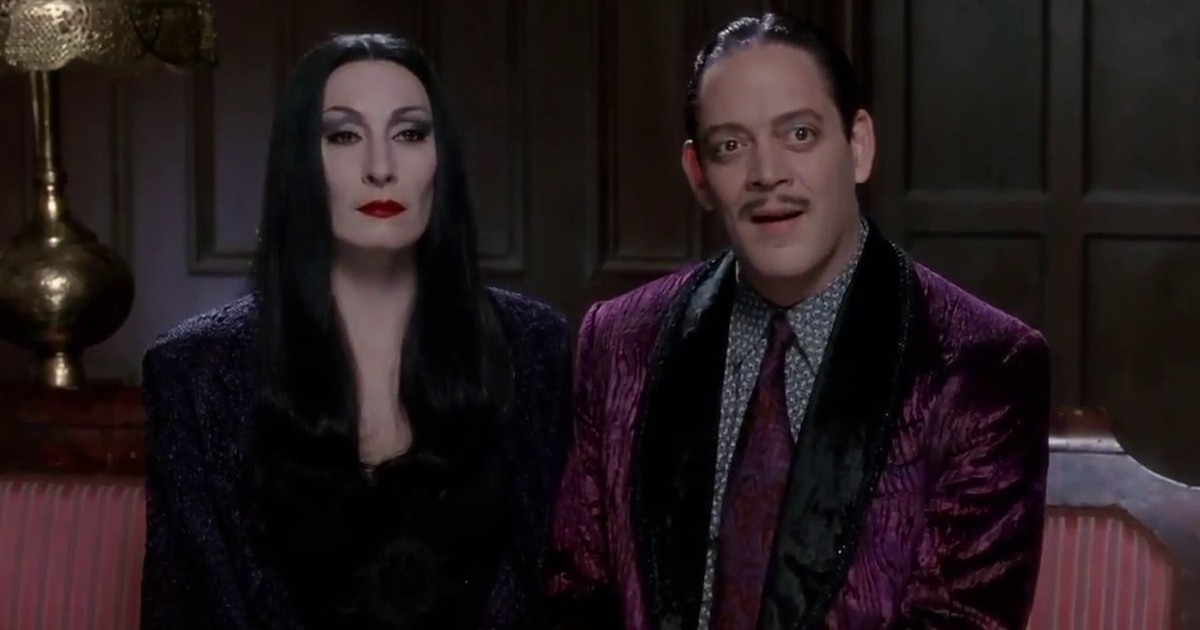 Morticia and Gomez Addams sitting together on a couch in 'The Addams Family'