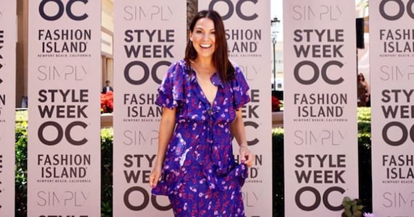 Simply founder Sarah Boyd standing in front of a step and repeat at Style Week OC at Fashion Island
