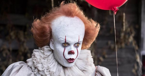 Pennywise holding a red balloon with a shocked look on his face in 'It'