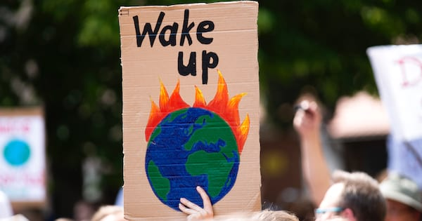 Person holding a cardboard sign with a painting of the earth on fire and the words \wake up\ written above it