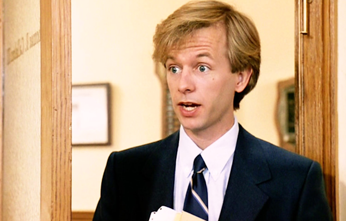 David Spade as Richard Hayden wearing a black suit and black tie in Tommy Boy